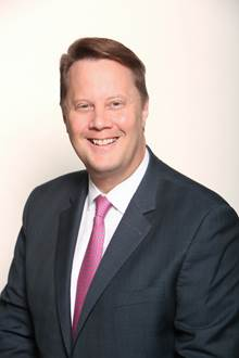 A person wearing a suit and tie smiling at the camera  Description automatically generated